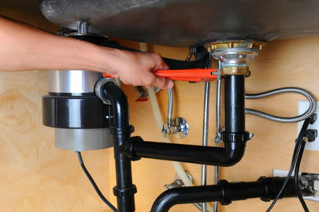 Plumber-Using-Wrench-Under-Kitchen-Sink